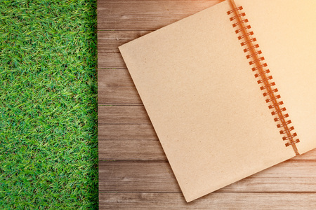 sketchbook: Open Vintage recycle Sketchbook on old wood plank texture background and green grass floor