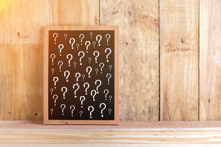 interrogative: blackboard with question mark symbol and free copy space for your text with wooden floor and wall background