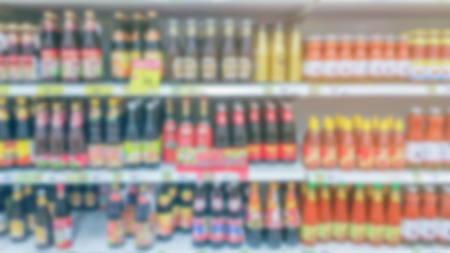 soft sell: blurred image of sauce bottle shelf in supermarket background usage Stock Photo