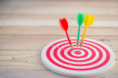 marketing target: target dart with arrow over wooden background ,abstract background to target marketing concept . Stock Photo