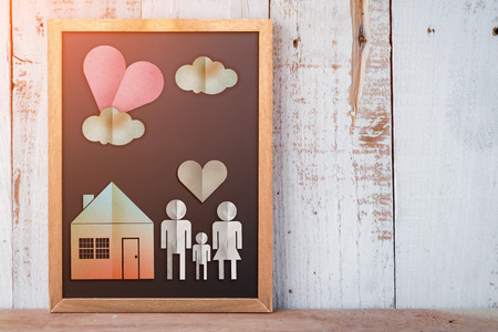 family house: home sweet home concept with family and house paper cut on chalkboard and wooden backgrund Stock Photo
