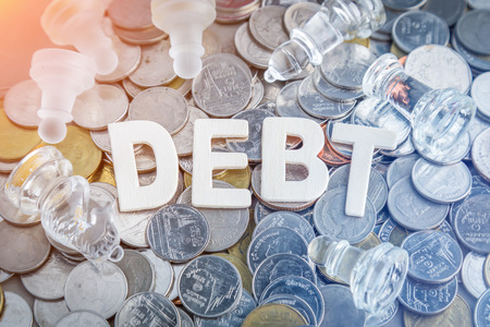 bad planning: Closeup wood letters of debt word with heap of coins business concept Stock Photo