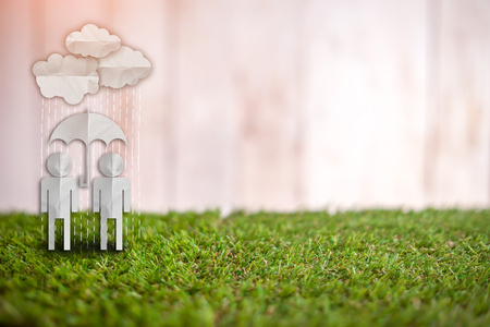 original single: couple people with rain umbrella paper cut on green grass floor and white color vintage wood background