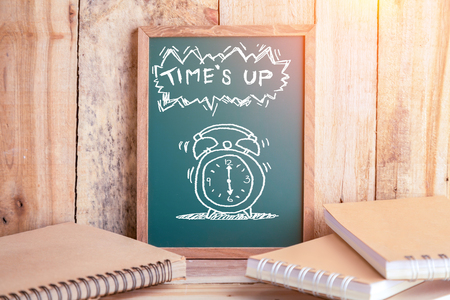 times up: drawing of alarm clock with times up word on chalkboard with notebook and wooden floor and wall with lighting flare effect