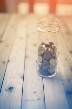 saving tips: Collection of coins in glass savings jar over wooden table business saving concept