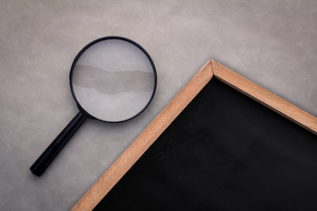 leather background: magnifying glass with chalkboard with copy space for your text on grey leather background