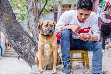 Lijiang, China - April 12, 2016: man is sitting with dog on the street in Lijiang, China