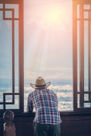 scenary: young man looking out of windows to beautiful landscape scenary