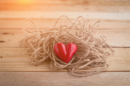love proof: Red heart  shape with  rope on wooden desk love problem concept Stock Photo