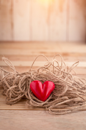love proof: Red heart shape with  rope on wooden desk love problem concept