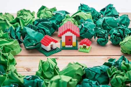 model of plastic house building with trash paper balls, loan, real estate or buying a new home concept.with copy space