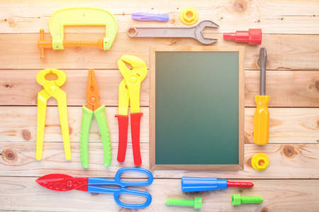 drill floor: Working tools toys and chalkboard on a wooden floor background. Including ruler, drill, nails, pliers,brush,thread,chisel and other.