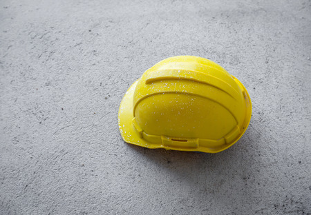hard hats: Yellow hard hats OR HELMET on concrete floor inside unfinished building construction concept