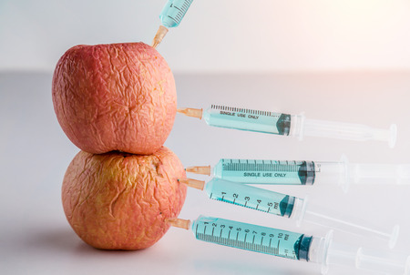 Injection into red apple - Concept for Genetically modified fruit and syringe with colorful chemical GMO food