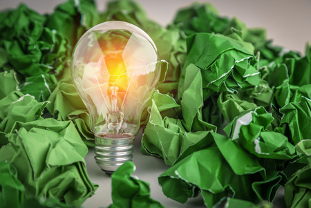 creativity business ideas concept with light bulb with green trash paper balls on white background