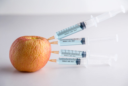 apple gmo: Injection into red apple - Concept for Genetically modified fruit and syringe with colorful chemical GMO food