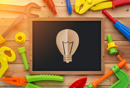 drill floor: light bulb paper cut on chalkboard on a wooden floor background. Including ruler, drill, nails, pliers,brush,thread,chisel and other ideas concept Stock Photo