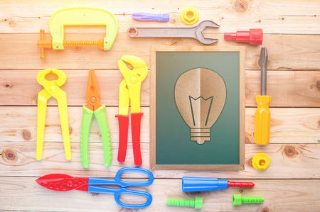 planking: light bulb paper cut on chalkboard on a wooden floor background. Including ruler, drill, nails, pliers,brush,thread,chisel and other ideas concept Stock Photo