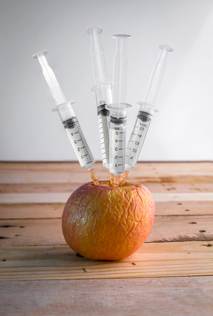 apple gmo: Injection into red rottrn apple - Concept for Genetically modified fruit and syringe with colorful chemical GMO food Stock Photo