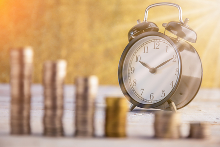 cronologia: coins stack and alarm clock on golden background business concept Foto de archivo