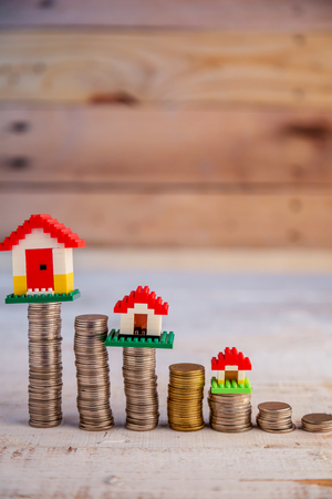 uk money: House models with stacked coins at wooden table background business asset concept