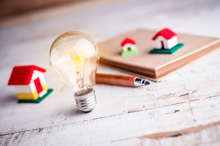 proprietary: light bulb and house model on notebook and white wooden background Stock Photo