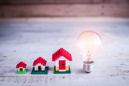 proprietary: light bulb with house model on wooden floor house ideas concept Stock Photo