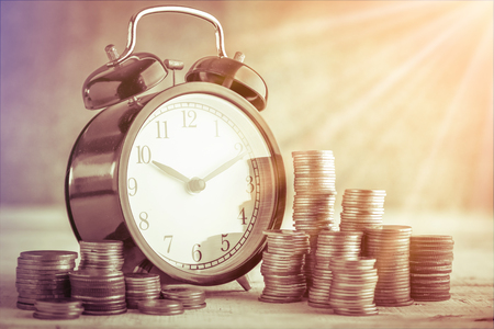 streamlining: coins stack and alarm clock on golden background business concept Stock Photo