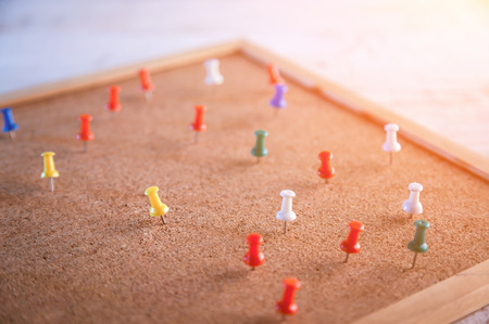 Group of colorful thumbtacks pinned on corkboard
