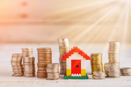property ladder: Minature houses resting on pound coin stacks concept for property ladder, mortgage and real estate investment Stock Photo