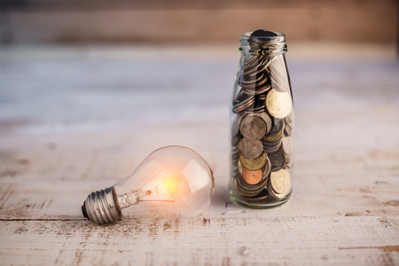 mony coin in bottle with glow light bulb business cocnept.jpg Stock Photo