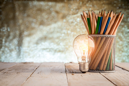 Wooden pencils in a black metal vase and light bulb on wooden floor and blur bokeh background business ideas concept