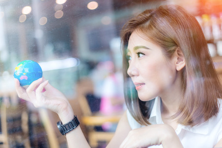cofffee: beautiful asian girl holding a globe  in her hand in cofffee shop with nature and light flare effect safe world concept