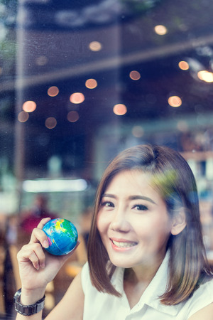 study: beautiful asian girl holding a globe  in her hand in cofffee shop with nature and light flare effect safe world concept