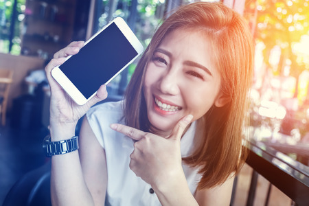 beauty asian girl smiling and showing smartphone with empty screen for your text  in cafe background
