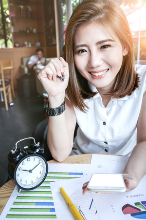 sunligh: beautyful Asia business woman working in a cafe with graph and paper sheet stuff Stock Photo