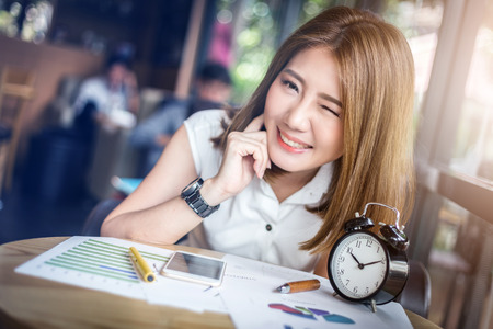 blink: cute happy asia girl blink eye working in coffeeshop with paper graph on wooden table with light flare effect