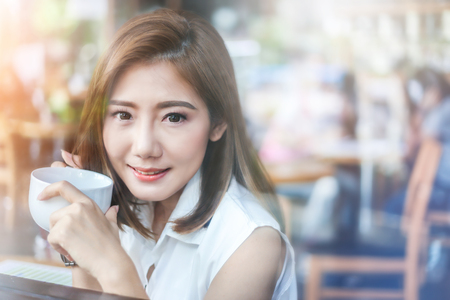 Portrait de femme asiatique souriante et tenant tasse de café avec fenêtre en verre réfléchissant rue ville flou bokeh Banque d'images