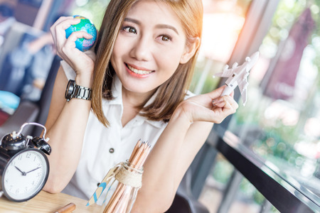 people, tourism, vacation and summer holidays concept - happy smiling young asian woman or teenage girl hold globe and plane toy in coffeeshop with light flare effect
