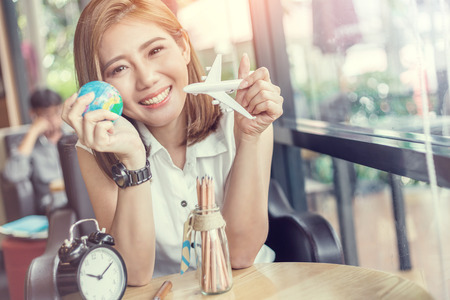 people, tourism, vacation and summer holidays concept - happy smiling young asian woman or teenage girl hold globe and plane toy in coffeeshop vintage color tone Archivio Fotografico