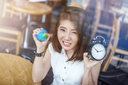 cofffee: beautiful asian girl holding a globe and black alarm clock in her hand with confused mood in cofffee shop with nature and light flare effect safe world concept Stock Photo