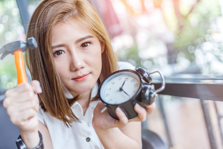 spall: beautiful asian girl try to hit black alarmclock in coffee shop business timing concept
