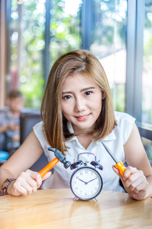 beautiful asian girl try to fixed black alarmclock on wooden table business timing concept