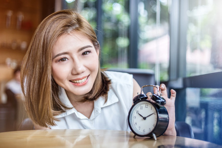 cute smiling girl with alarm clock on wooden table in cafe with daylight flare effect