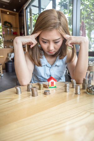 asia woman with house model and money bottle with stress and decision making business concept