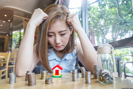 asia woman with house model and money bottle with stress and decision making Stock Photo