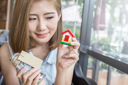 sold small: asian woman with a small house and coin in glass bottle thinking concept Stock Photo