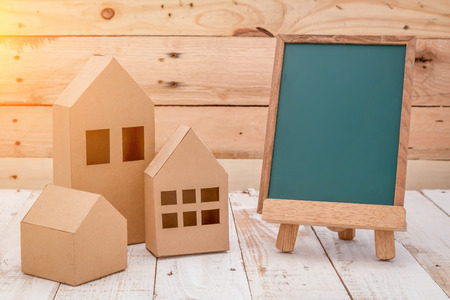 room for text: FRONT view of empty blackboard with room for text and house shaped paper cut over wooden table