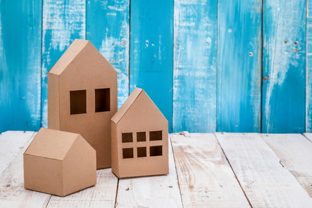 building loan: model of cardboard house on wooden floor and background. house building, loan, real estate or buying a new home concept.