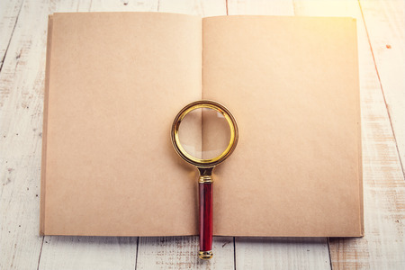 rummage: blank page notebook with a magnifying glass on a wooden background free copy space